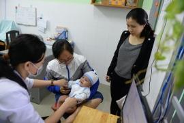 Người dân đưa con khám bệnh tại Trung tâm Y tế dự phòng Bình Chiểu, Q.Thủ Đức, TP.HCM - Ảnh: HỮU KHOA